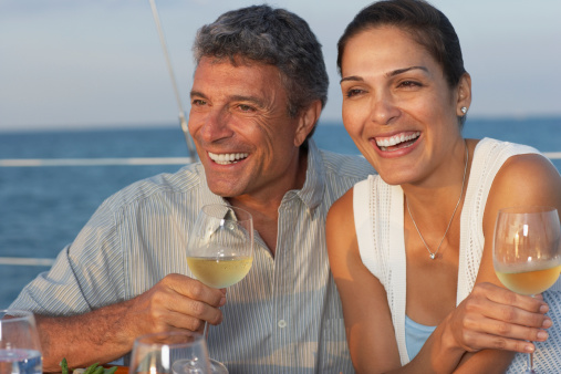 Couple sit on boat with wine