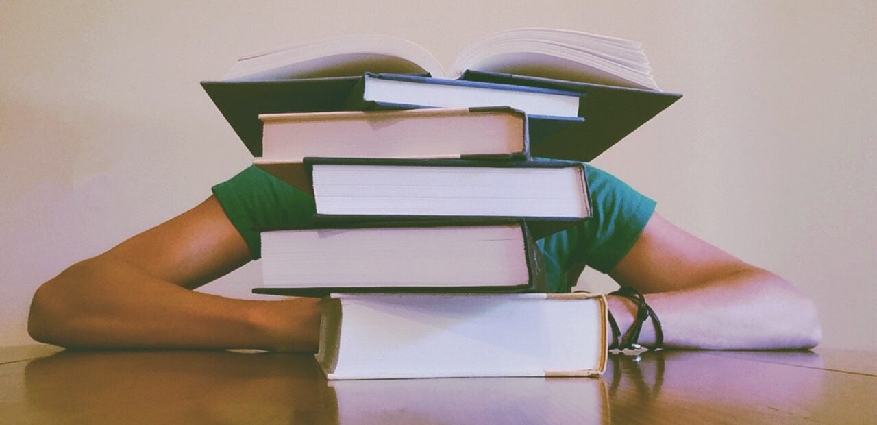 College kid sleeping behind books