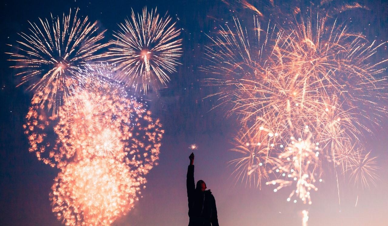 Fireworks behind a kid holding a sparkler