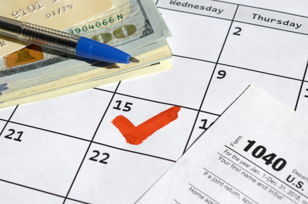 1040 individual income tax return blank with credit card on dollar bills and pen on calendar page t20 drlzVl | Bogart Wealth