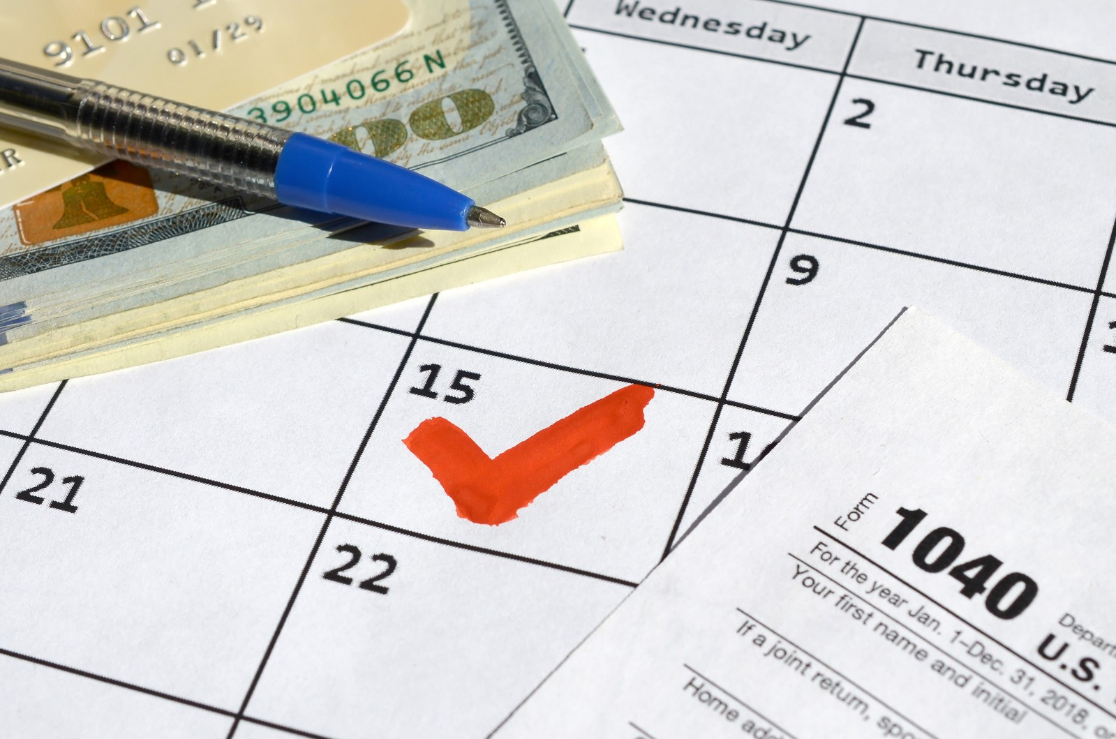 Cash and a 1040 tax form on a calendar