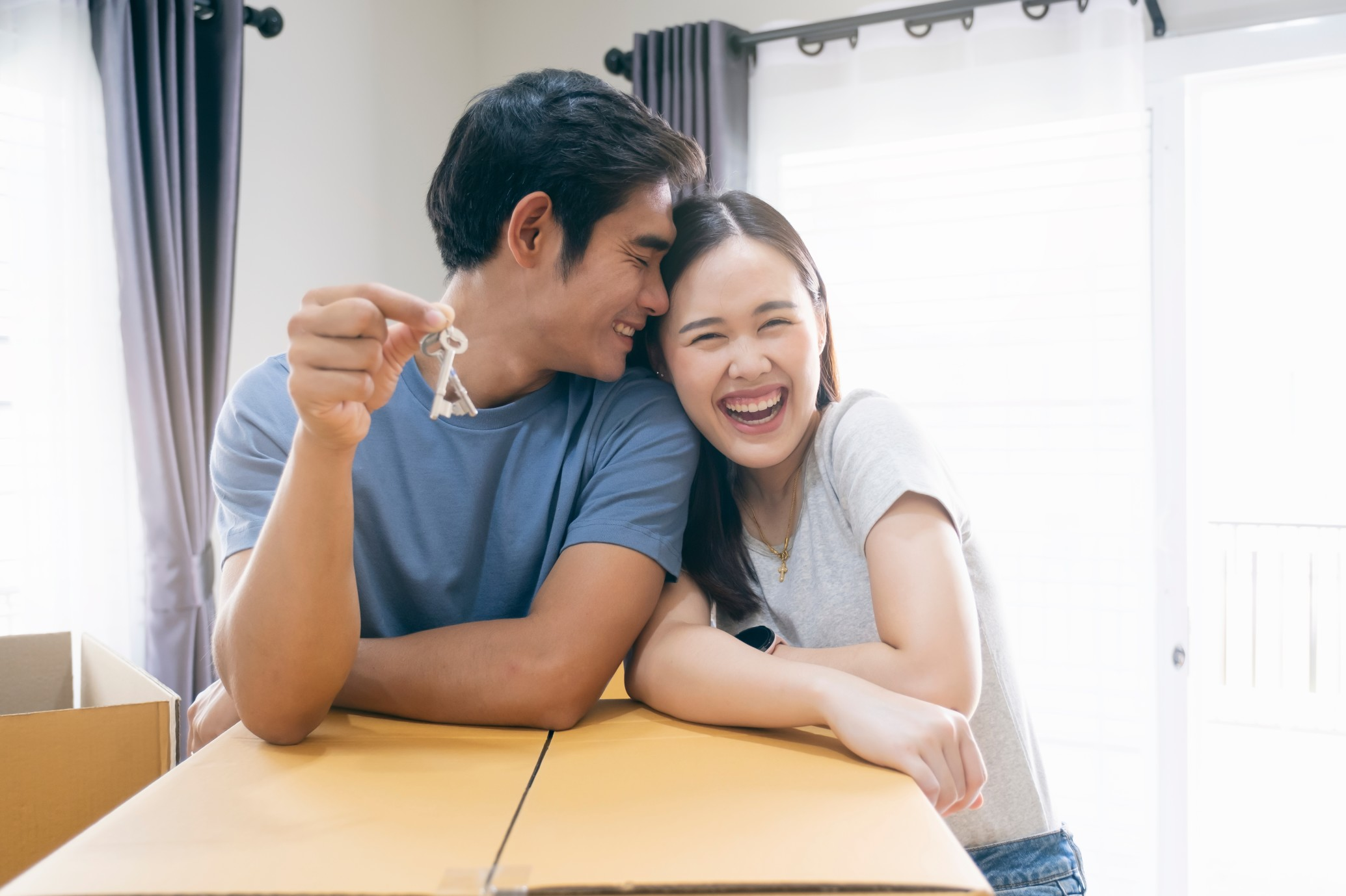 happy young couple enjoying together moving in a new house new house at moving | Bogart Wealth