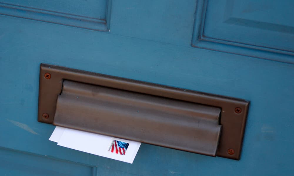 A letter from the IRS coming through a door mail slot.