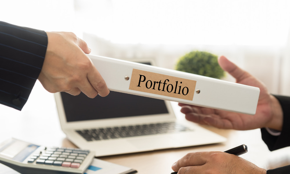 Person handing over binder of portfolio performance