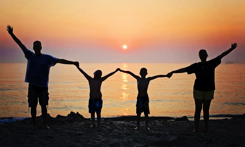 A family holding hands on a beach in front of a sunset