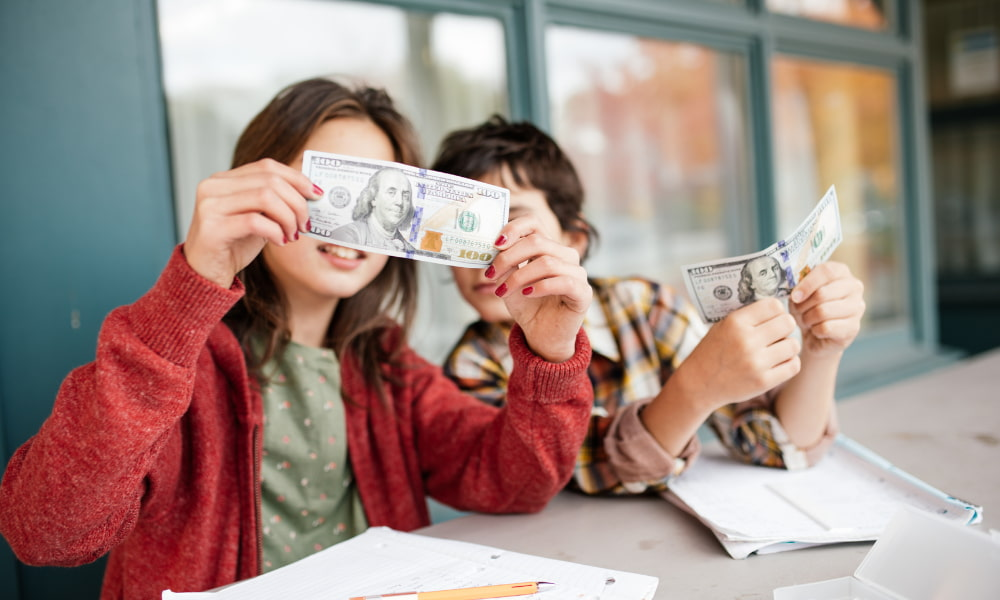 Kids sitting at a table holding 100 dollar bills