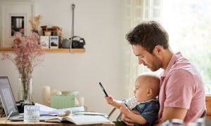 Man sitting at a computer with a child in his lap, doing financial planning for a baby