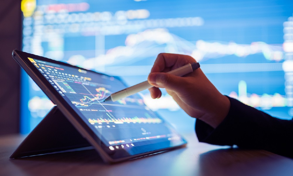 A pen pointed at a tablet screen that displays data relating to the returns of bonds and stocks used in a barbell investment strategy
