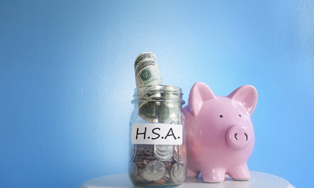 """Table with a jar labeled """"H.S.A."""" full of coins and dollar bills and a pink piggy bank next to it, illustrating an HSA investment strategy."""