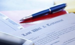 A mobile phone and a ballpoint pen on top of a last will and testament document that contains a codicil to update the will