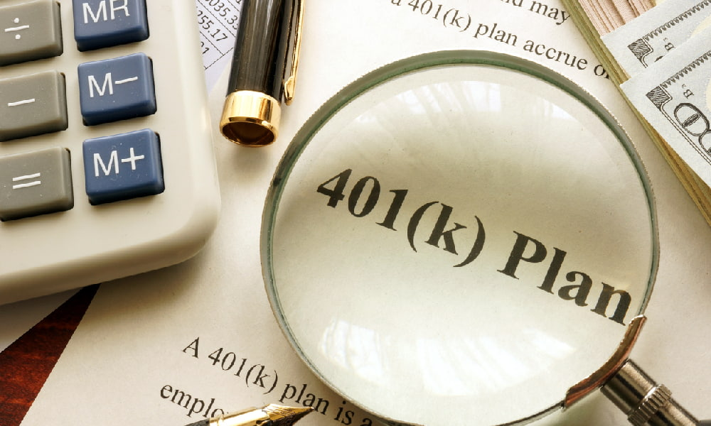 """Magnifying glass over a piece of paper that reads """"401(k) Plan"""" surrounded by pens, a calculator, and other papers, signifying an investor pondering options for a 401(k) after retirement."""