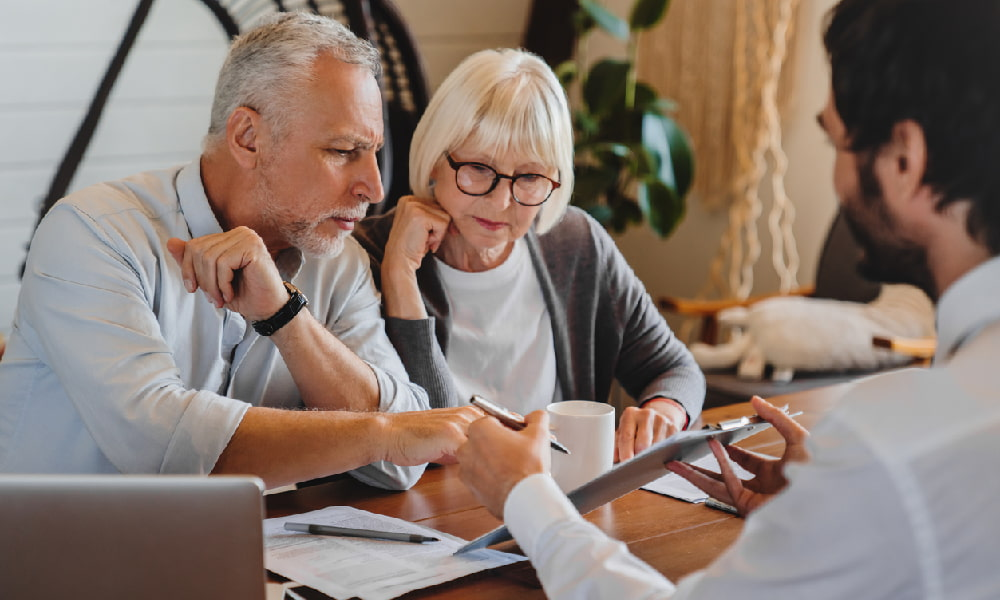 An elderly couple sits at a desk and looks at a tablet while talking with a financial advisor about avoiding retirement mistakes.