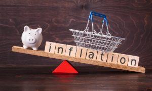 """The word """"inflation"""" spelled on wood-block tiles with a shopping basket and a piggy bank on a seesaw, signifying our guide on how to protect against inflation."""