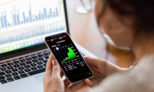 An investor reads a financial chart on her phone to decide between options vs. stocks.