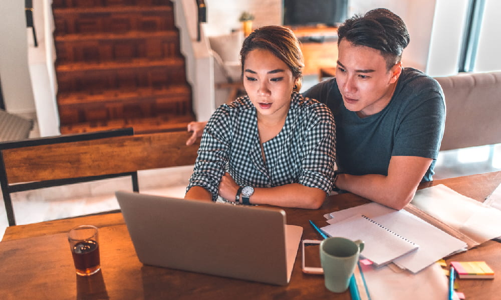 a young couple using a laptop and creating long-term financial goals.