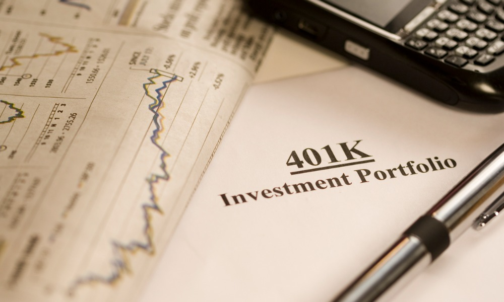 401(K) document, some charts, and other elements of a retirement portfolio sitting on a desk.
