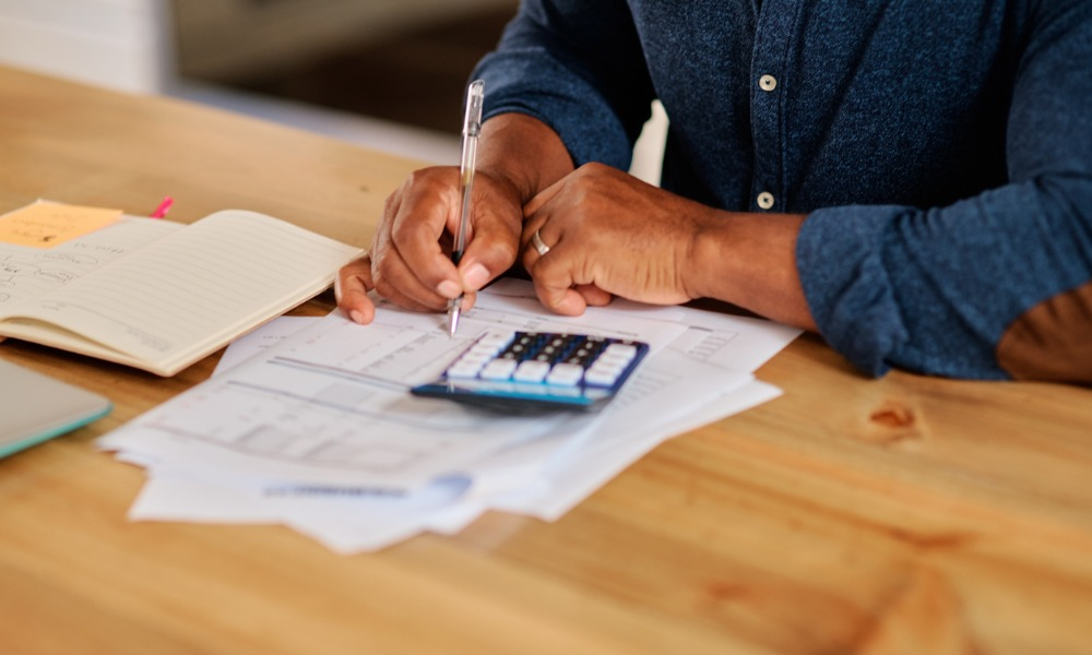 man applying the rule of 70 to his investments while sitting at a desk with documents and a calculator.