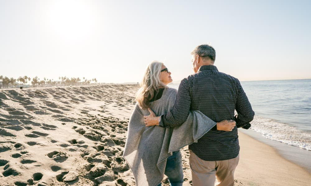 A couple enjoys a walk on the beach because they took preparation for retirement seriously.