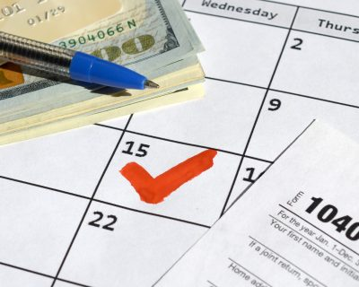 1040-individual-income-tax-return-blank-with-credit-card-on-dollar-bills-and-pen-on-calendar-page_t20_drlzVl