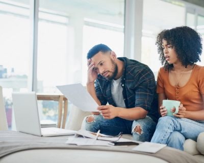 Couple sitting on couch, stressed out over student loan debt
