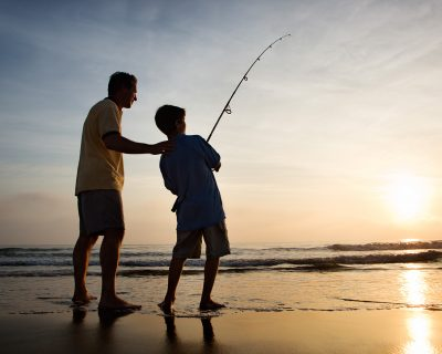 Father and son fish looking at sunset