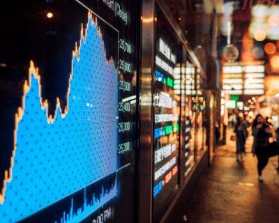 international stocks rising on a tv screen near the street